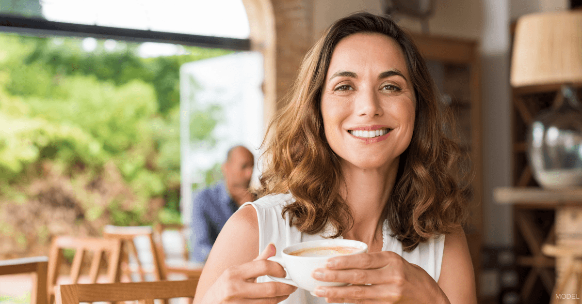Woman with a cup of coffee considering laser skin resurfacing and chemical peel treatments in Burlington, ON